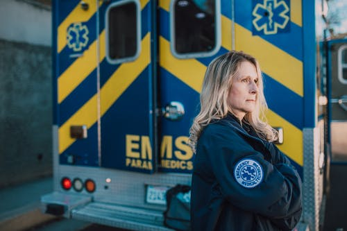 Woman in Blue Jacket Standing Near Yellow and Blue Ambulance