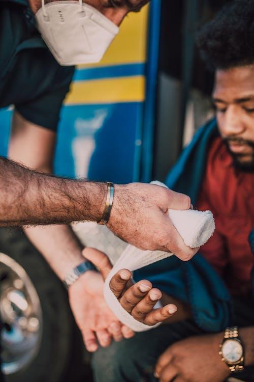 Paramedic Putting Bandage On Man's Hand