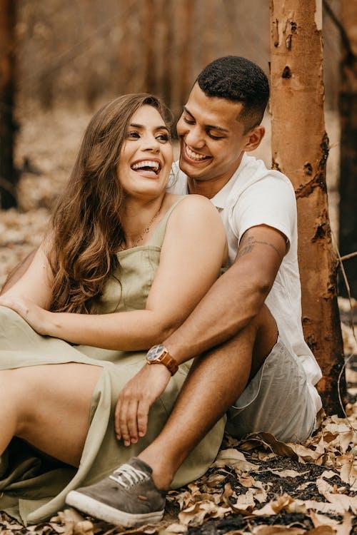 Joyful multiethnic couple embracing near tree