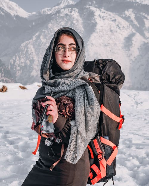 Woman in Black Coat and Black Scarf Standing on Snow Covered Ground