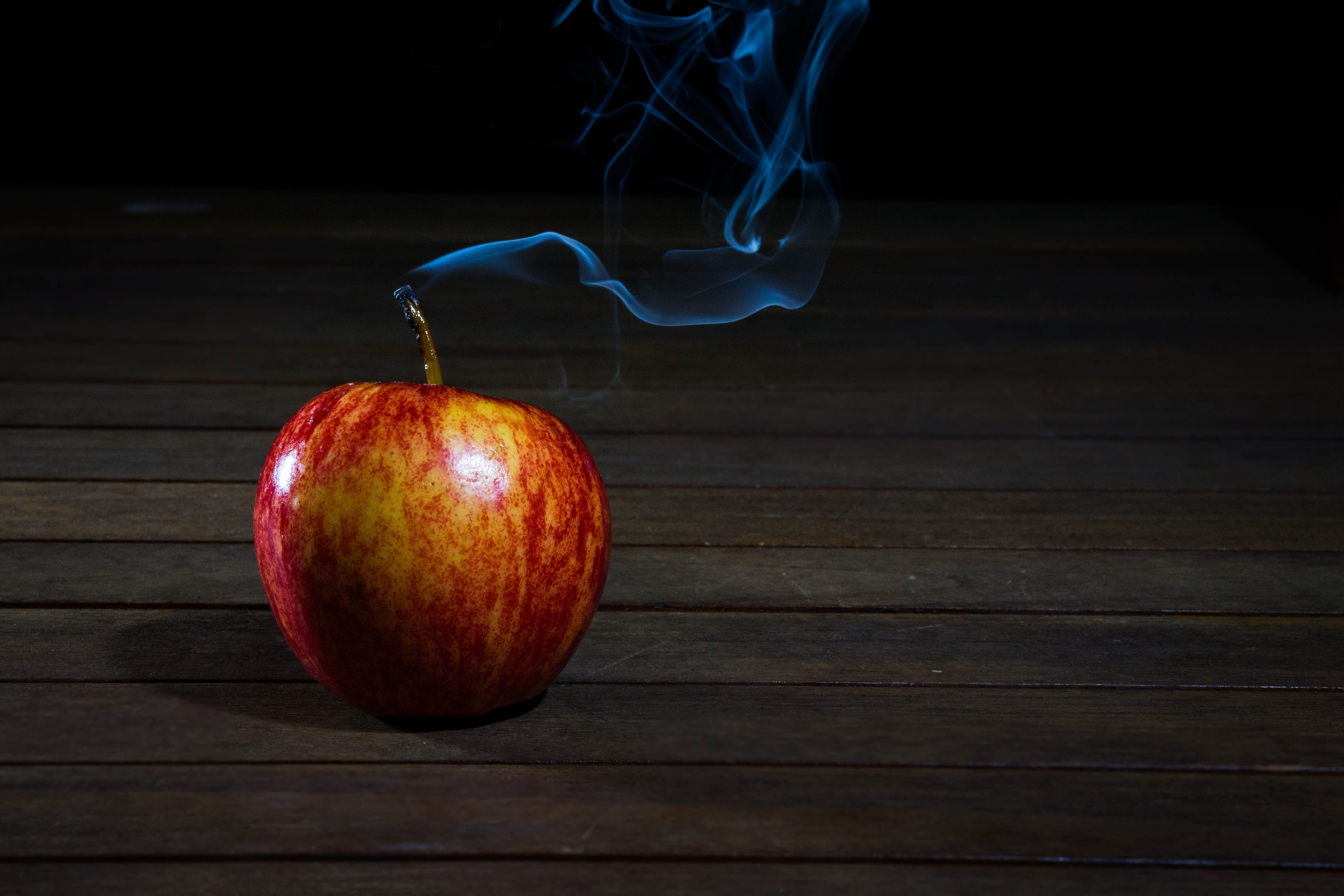 Red Apple With Smoke Coming from Stalk on Wooden Floor