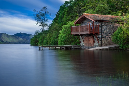 Brown Cottage Near Blue Body of Water during Daytime