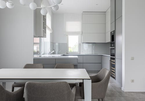 Contemporary interior of cozy kitchen with clean white new comfortable furniture in daytime