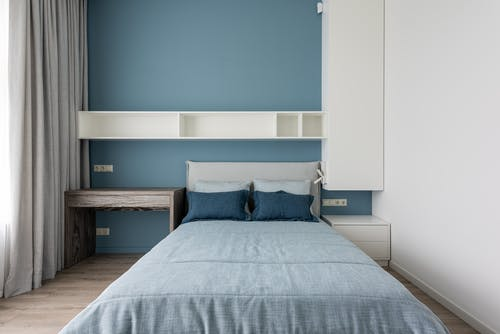 Modern bedroom with empty shelves and soft comfortable bed