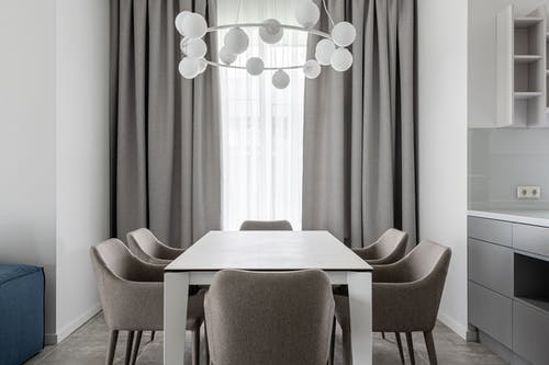 Comfortable simple dining room with rectangular shaped table surrounded with cozy chairs near window with curtains