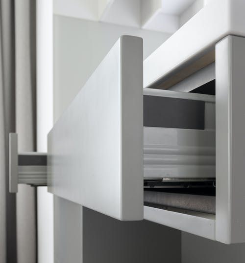 Contemporary expensive cabinet with clean white drawers in modern residential apartment in daytime