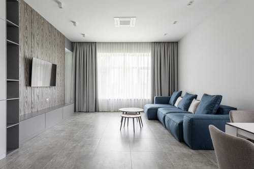 Modern spacious lounge with soft sofa and TV