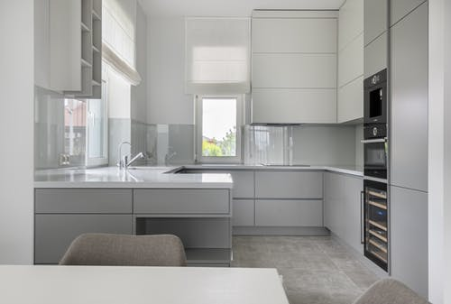 Interior of contemporary new prestige kitchen with modern equipment and white furniture in daylight