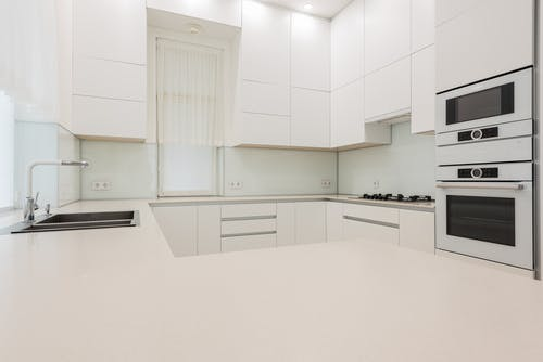 Interior of contemporary kitchen with white expensive cupboards in minimal design in bright lights
