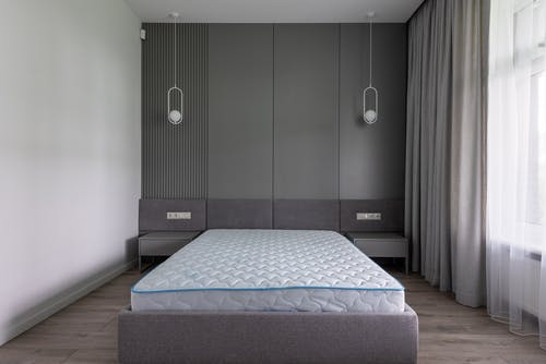 Comfortable bed with convenient modern mattress in contemporary interior of spacious gray bedroom