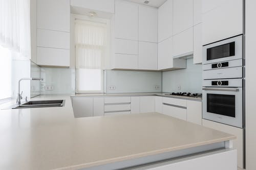 Interior of modern simple kitchen with white furniture and expensive equipment in daytime