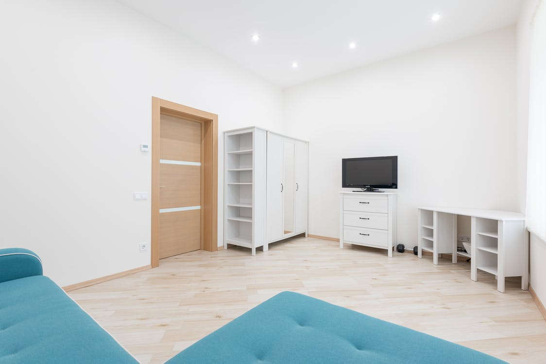 Interior of modern apartment with turquoise couch placed against wall with TV set and white table with closet in apartment