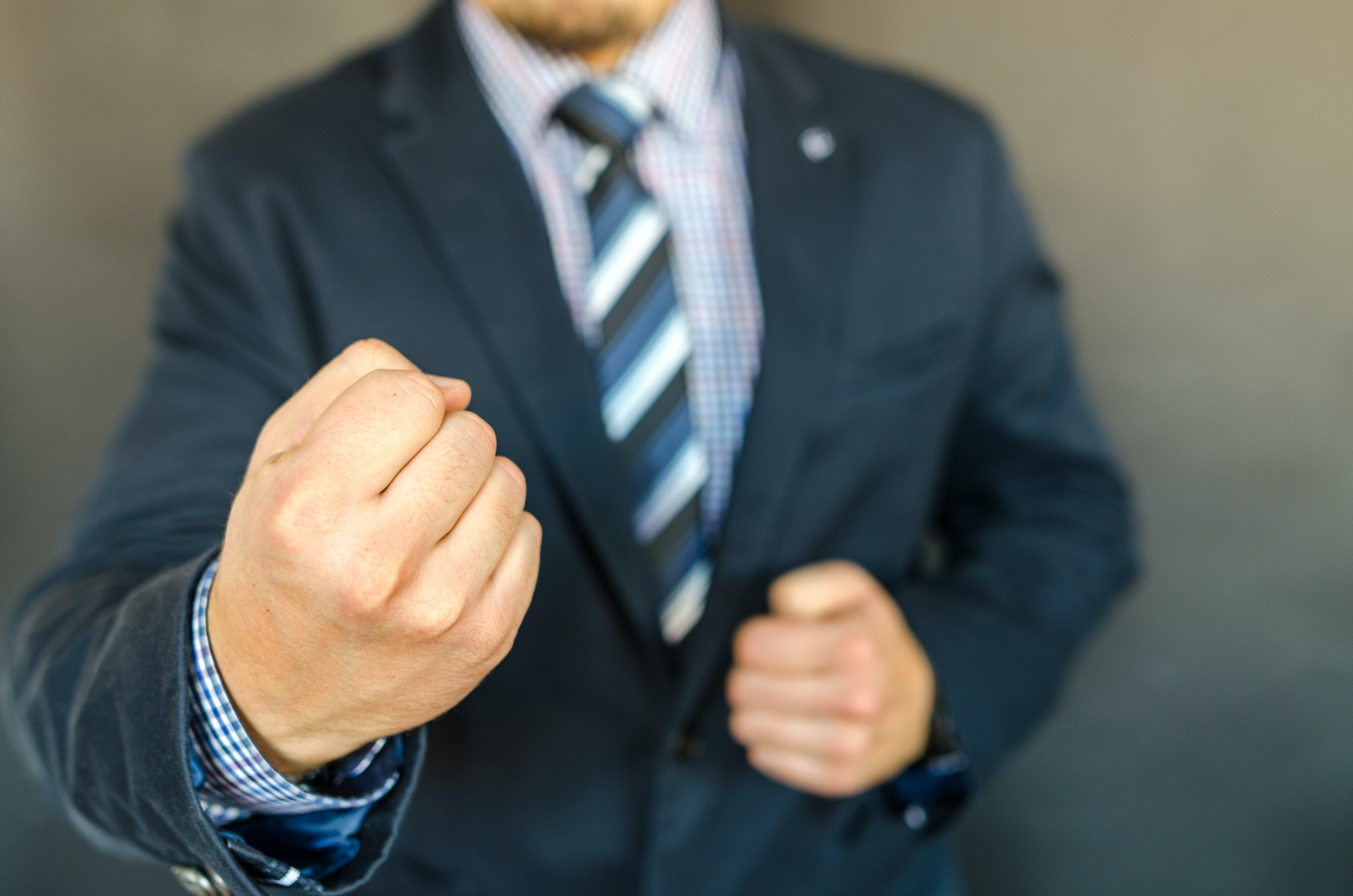 A man holding his fists up - he's ruthless when making decisions.