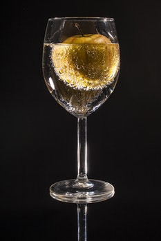 Clear Wine Glass Filled With Clear Beverage With Yellow Round Fruit