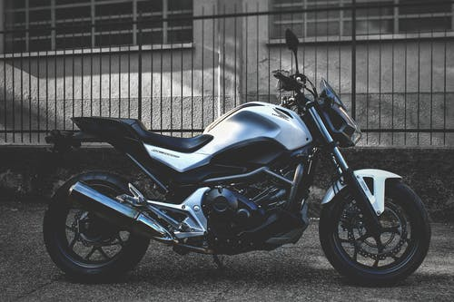 Black and Blue Naked Motorcycle Parked Beside Gray Metal Fence