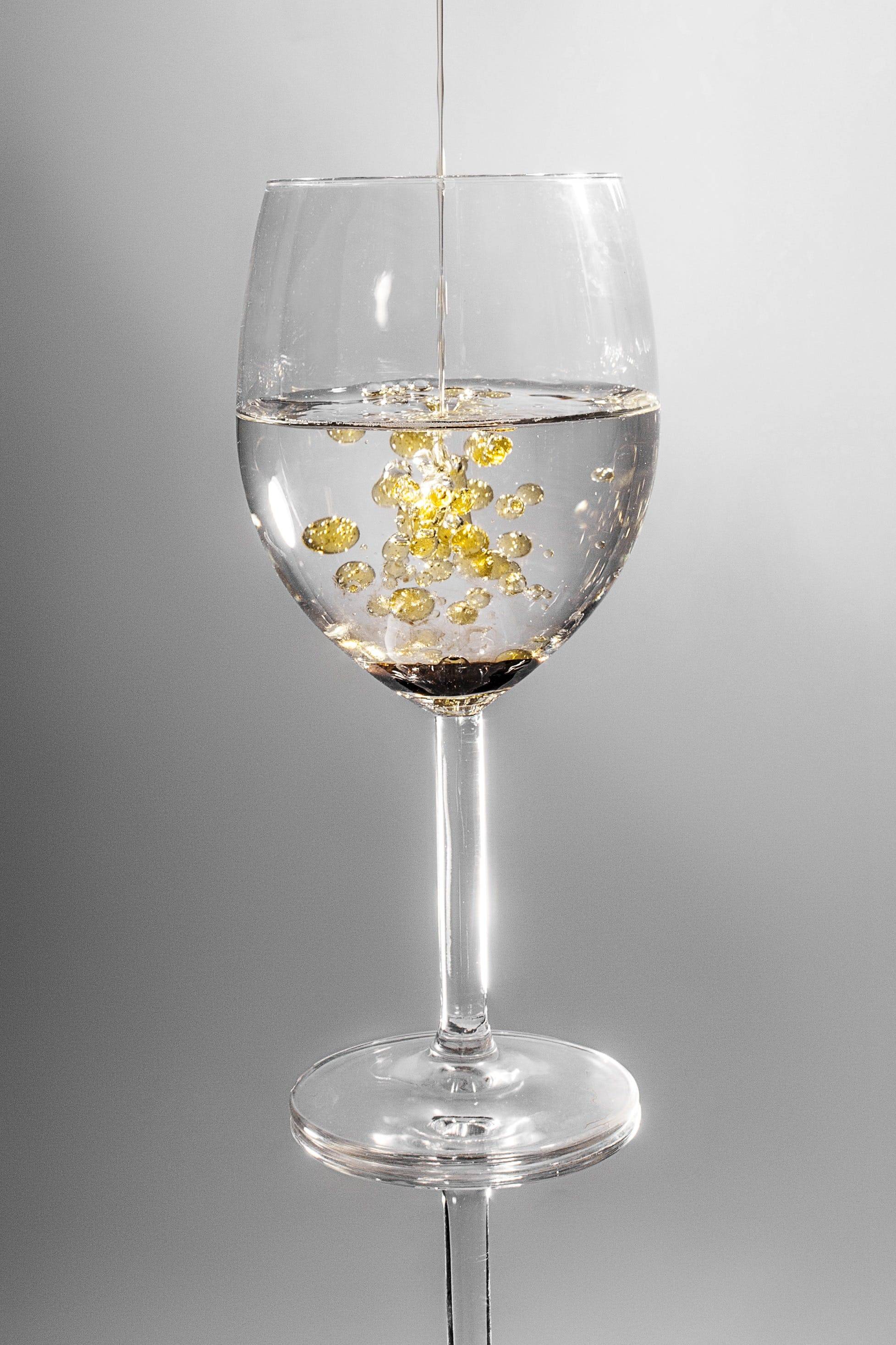 Clear Long Stem Wine Glass With Yellow Liquid