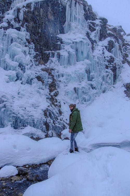 Traveler standing near brook and frozen waterfall