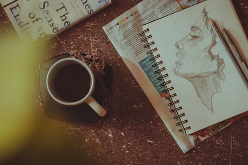 From above of sketchbook with person portrait near pen and pencil next to mug with drink on saucer with herbs on table near book and newspaper in light room