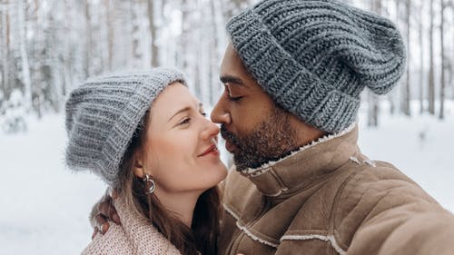 Romantic young diverse couple hugging in snowy forest on winter day