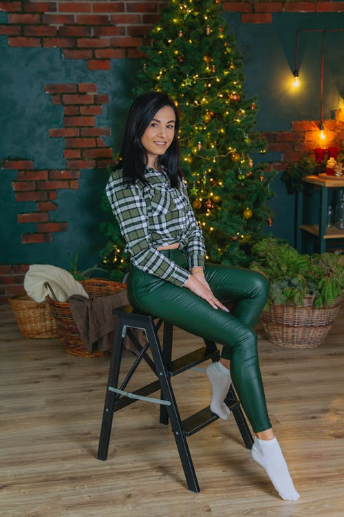 Full body of cheerful female looking at camera while sitting on chair in decorated room with fir against brick wall