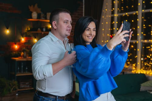 Cheerful couple taking selfie in decorated room