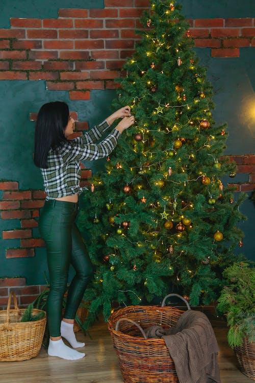 Stylish woman decorating Christmas tree