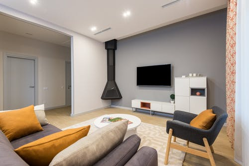 Interior of spacious room with comfortable couch with cushions and armchair placed against wall with TV and white cupboards in apartment with fireplace