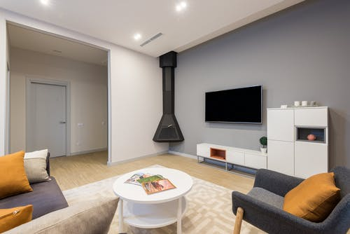 Interior of modern living room with comfortable sofa and armchair placed near side table against wall with TV and cupboards near fireplace