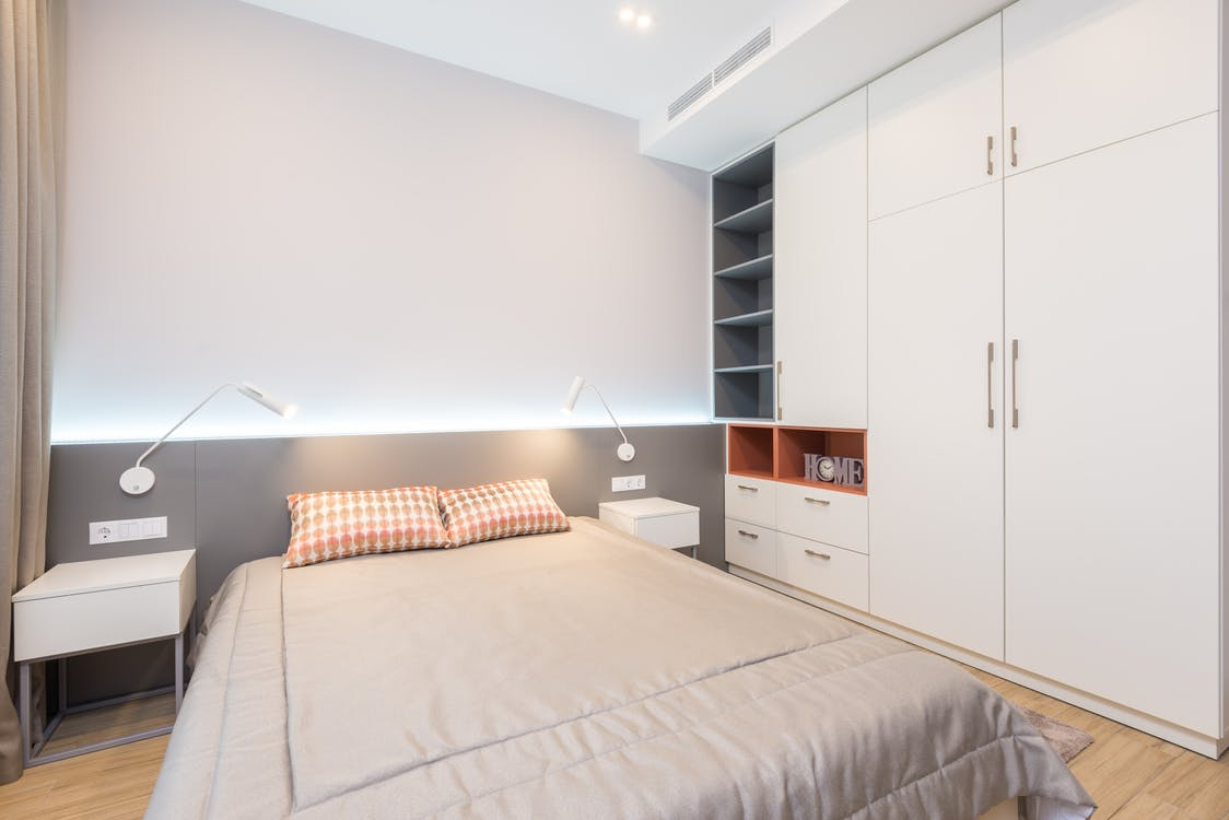 Comfortable bed with pillows placed near bedside tables and white wardrobe in modern spacious bedroom with glowing lamps in apartment