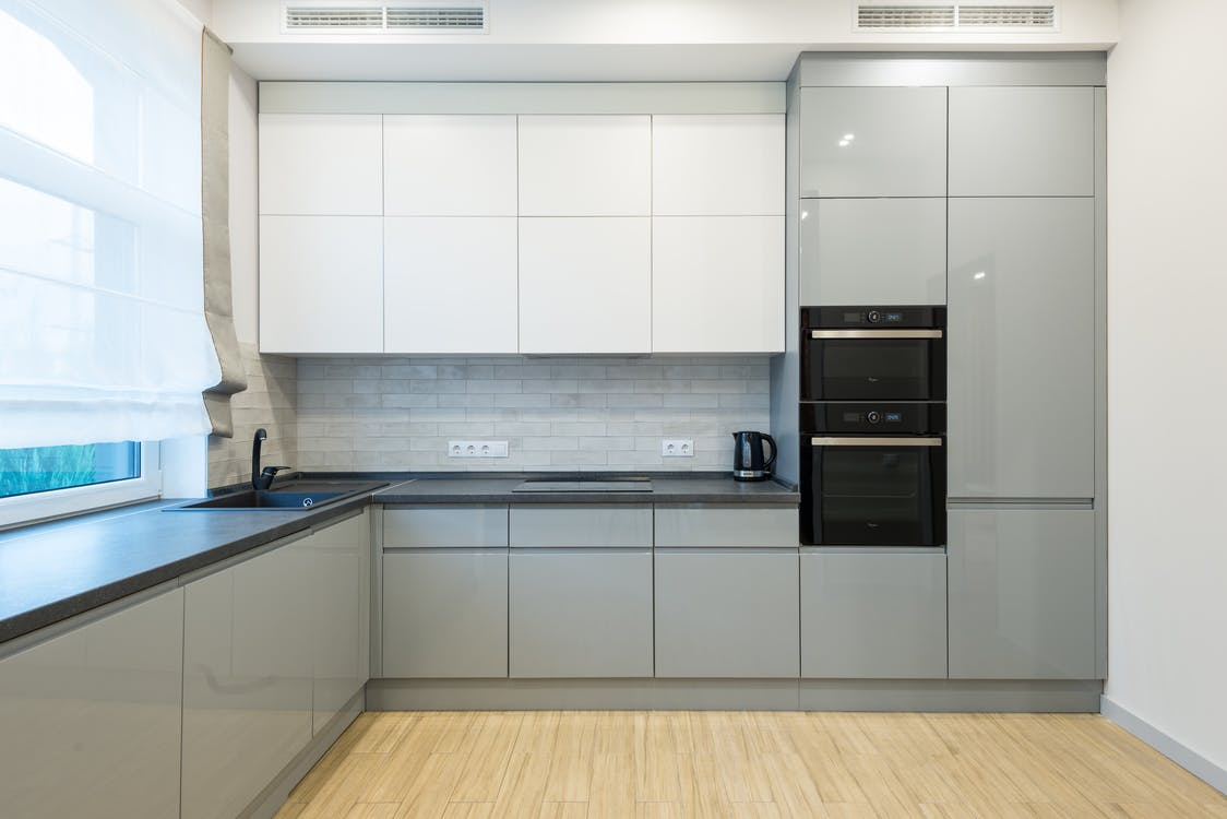 Interior of contemporary kitchen with gray and white cabinets with sink and modern oven near electric cooker in spacious apartment
