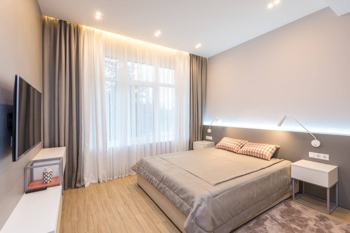 Comfortable bed with cushions and blanket placed between bedside tables with glowing lamps against TV set in modern bedroom with window