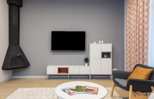 Modern TV and fireplace hanging on wall in minimalist apartment with white furniture and comfortable armchair