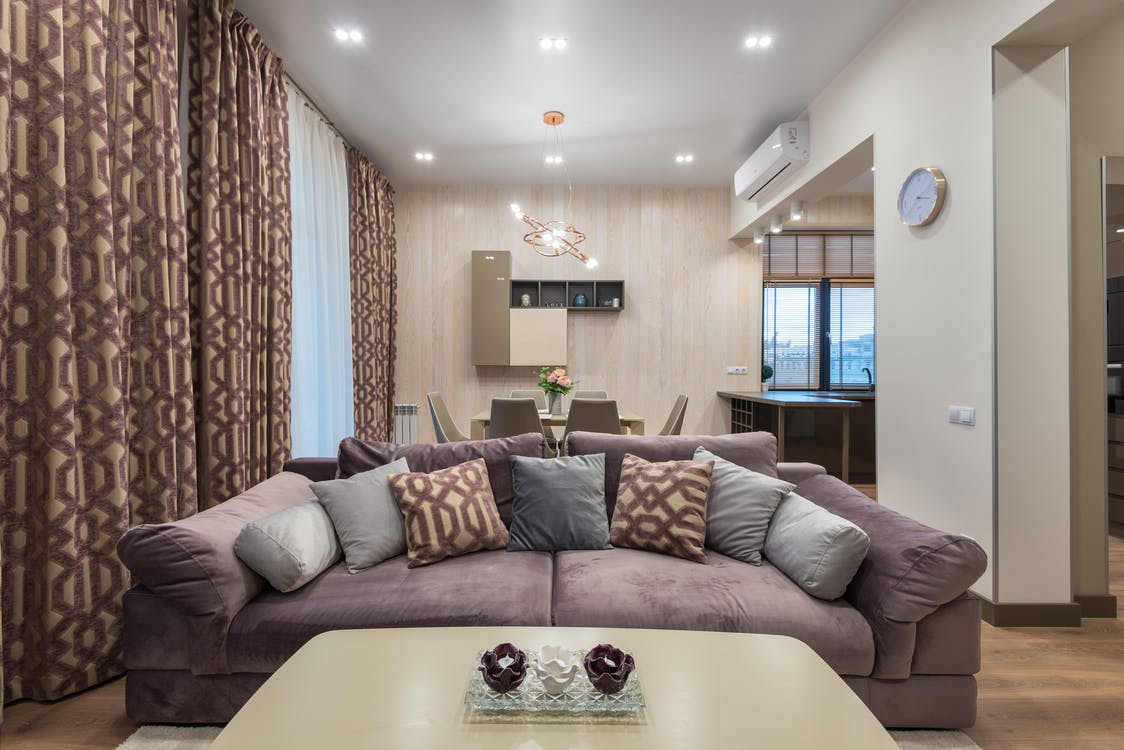 Soft comfortable couch with various cushions and coffee table placed in cozy living room with dining zone