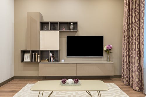Coffee table placed on carpet near modern TV set and minimalist cabinet decorated with vase of flowers in living room