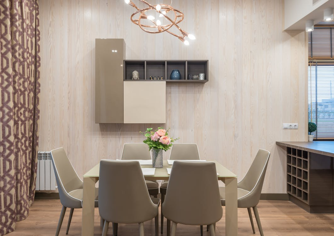 Comfortable chairs and table decorated with vase of fresh flowers placed in modern apartment with minimalist interior