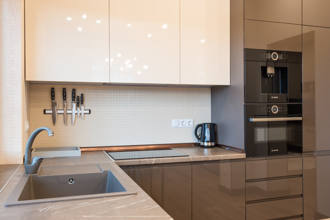 White Wooden Kitchen Cabinet and Stainless Steel Faucet