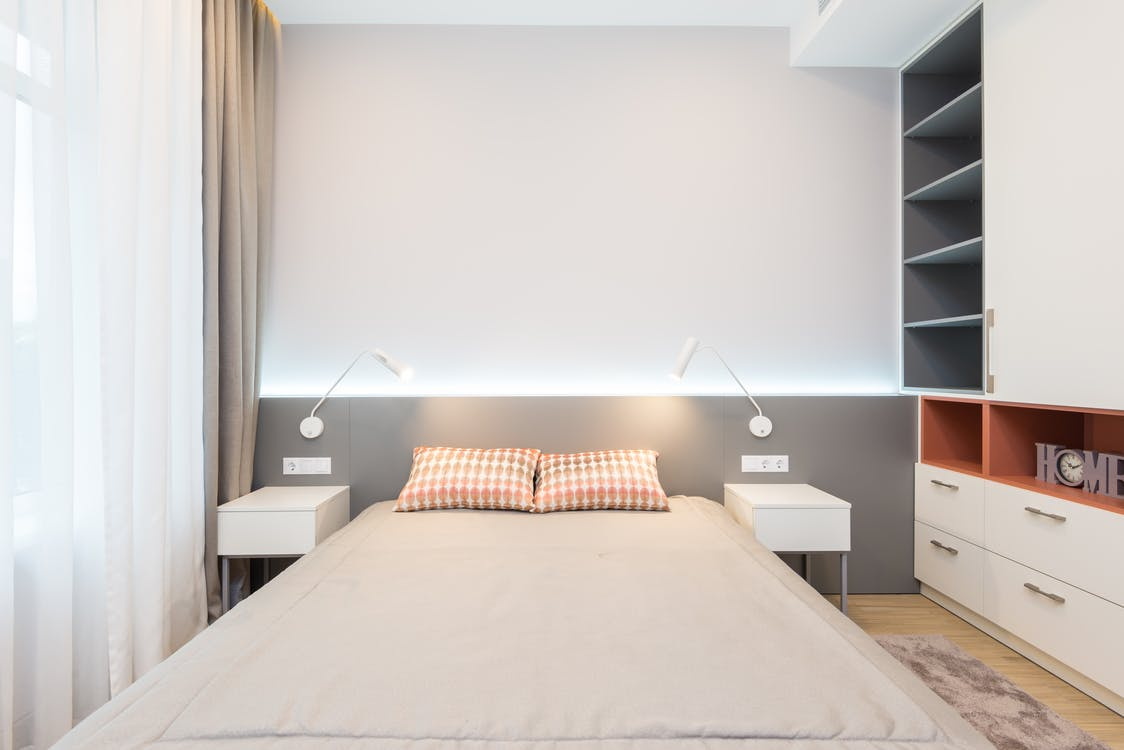 Cozy bed with nightstands and wardrobe in light bedroom