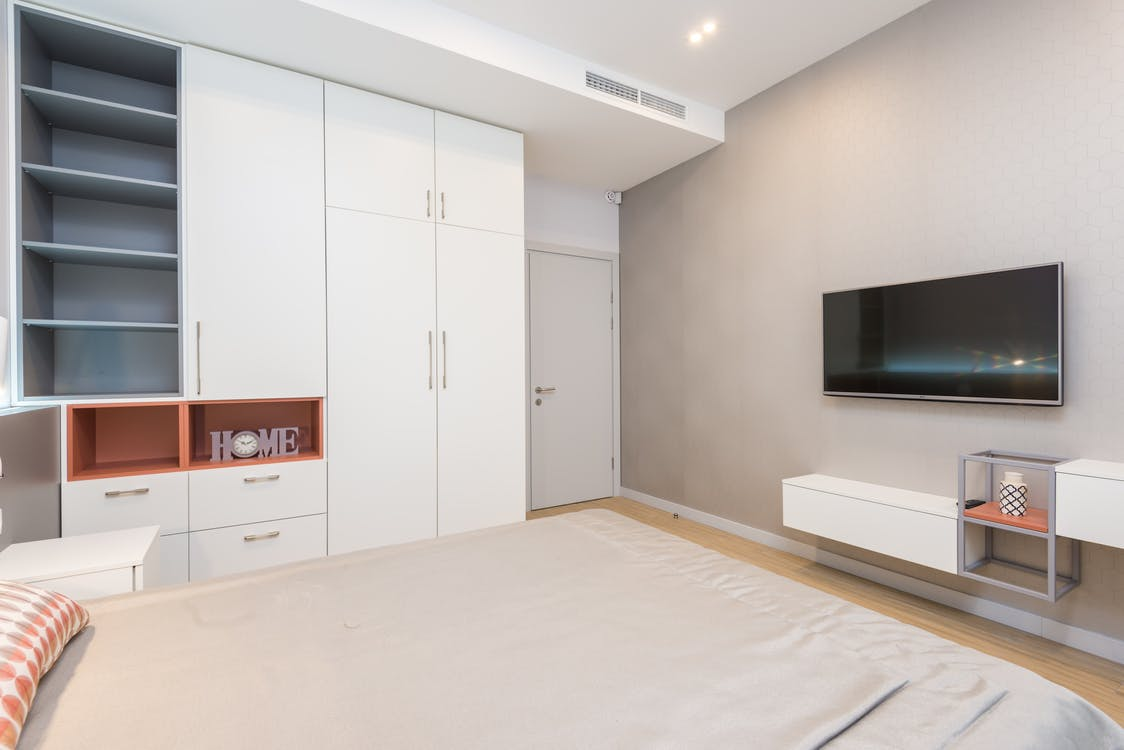 Modern TV set hanging on wall in front of comfortable bed in cozy bedroom with white furniture