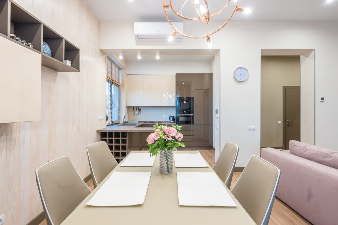 Dining table with chairs and kitchen zone in modern studio apartment with comfortable couch and white walls