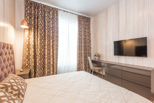 Comfortable bed with soft cushions and headboard in classic styled bedroom with modern TV set and chair