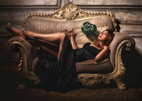 Woman in Black Dress Lying on Brown Couch