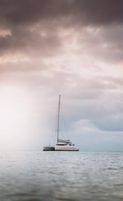 White Sailboat on Sea Under Dark Clouds
