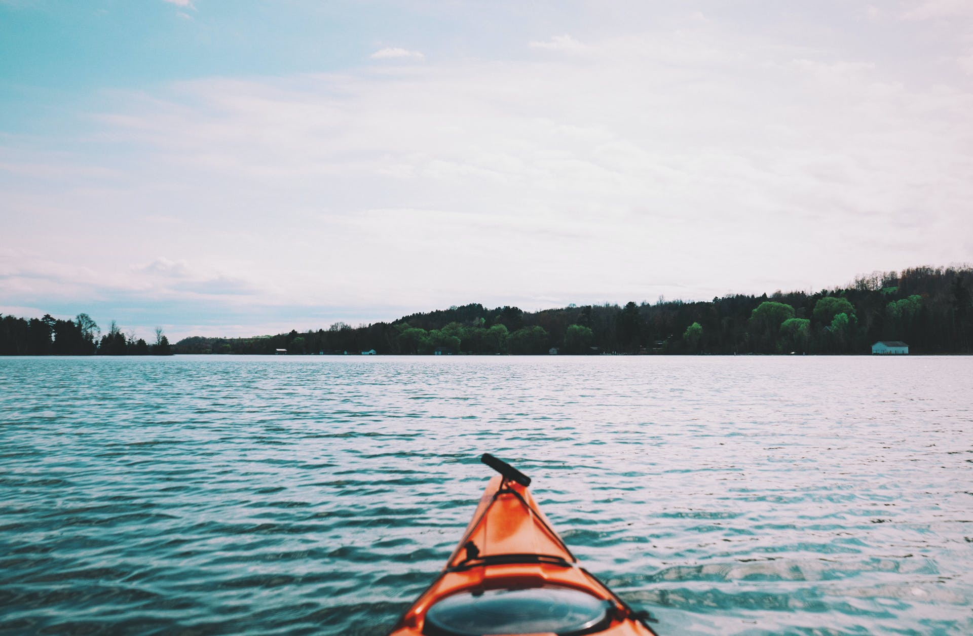 Person Riding Orange Kayak in Middle of Ocean