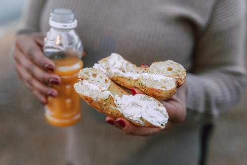 A Person Holding a Creamy Donut and Orange Juice