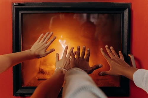 Couples Hands By Fireplace