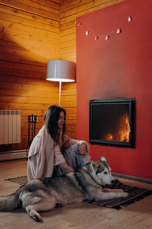 Woman with Her Dog Near the Fireplace