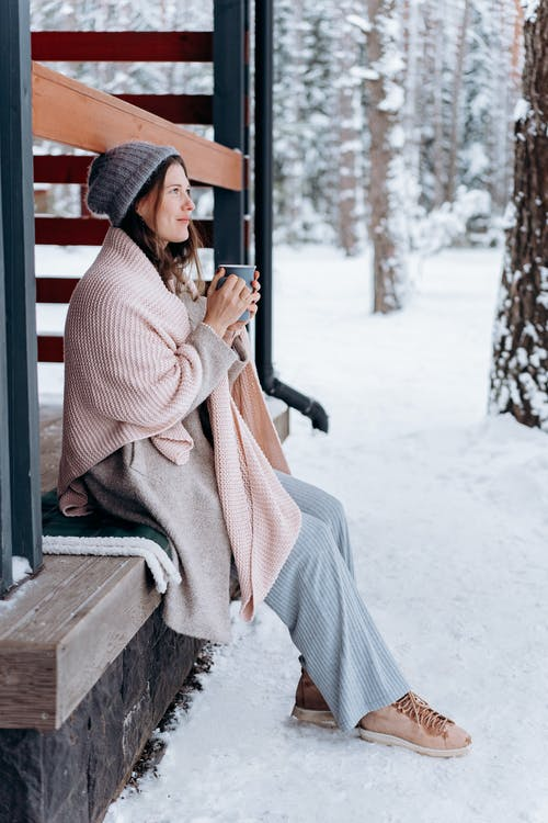 Woman Sitting On The Porch Holding A Cup With Hot Drink