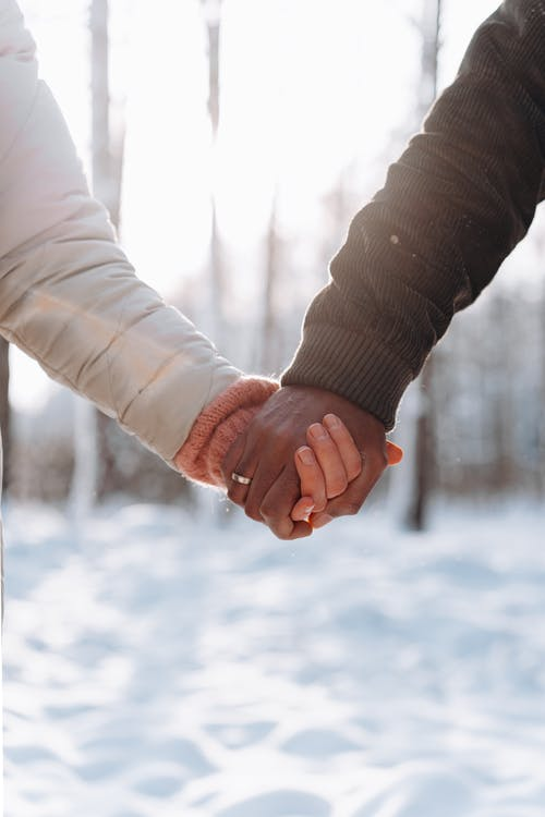 Person in Black Long Sleeve Shirt Holding Hands With Snow