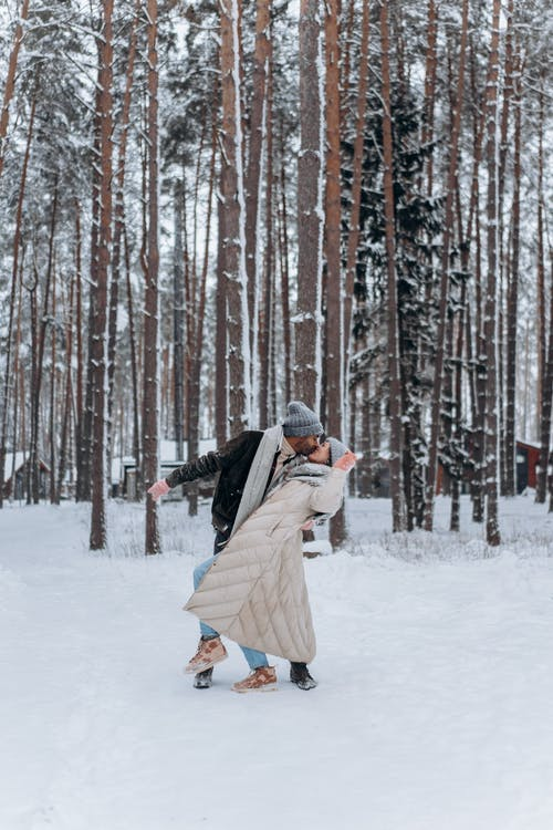 A Couple Kissing in the Snow Covered Forest