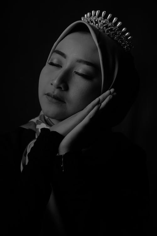 Calm ethnic lady in hijab touching face with closed eyes